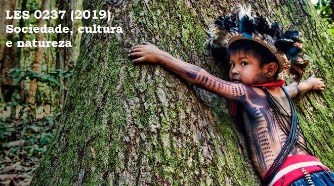 """Menino da tribo Tupi-mondé com pinturas no corpo e cocar abraçando uma árvore enorme e os dizeres """"LES 0237 (2019) Sociedade, cultura e natureza"""""""